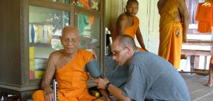 Health care professional in Thailand helping a monk.