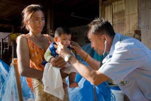 Health care professional in Thailand helping a baby.
